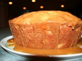 An apple cake covered in caramel frosting.